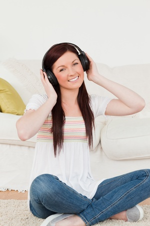 Good looking red-haired woman listening to music with headphones while sitting on a carpet in the living room photo