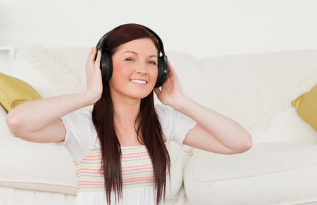 Beautiful red-haired woman listening to music with headphones while sitting on a carpet in the living room photo