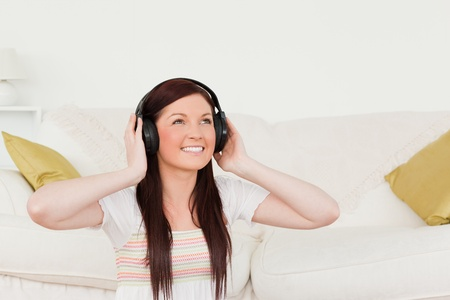 Pretty red-haired woman listening to music with headphones while sitting on a carpet in the living room photo