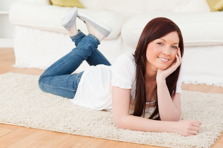 Smiling red-haired woman posing while lying on a carpet in the living room Stock Photo - 10205272