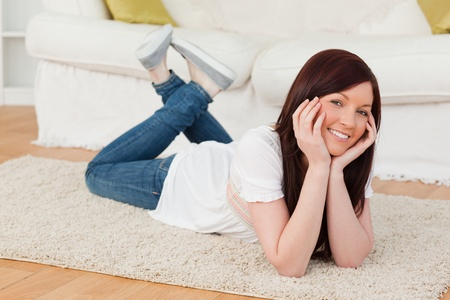 Beautiful red-haired woman posing while lying on a carpet in the living room photo