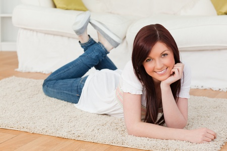 Attractive red-haired woman posing while lying on a carpet in the living room Stock Photo - 10205978