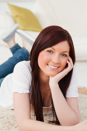 Joyful red-haired woman posing while lying on a carpet in the living room Stock Photo - 10205872