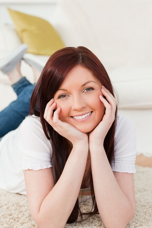 Happy red-haired woman posing while lying on a carpet in the living room photo