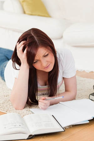 Pretty red-haired girl studying for while lying on a carpet in the living room photo