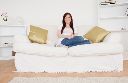 Beautiful red-haired woman posing while sitting on a sofa in the living room Stock Photo - 10197759