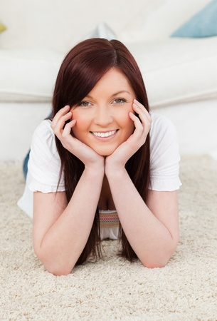 Attractive red-haired female posing while lying on a carpet in the living room Stock Photo - 10198374