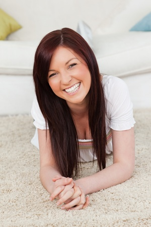 Pretty red-haired female posing while lying on a carpet in the living room photo