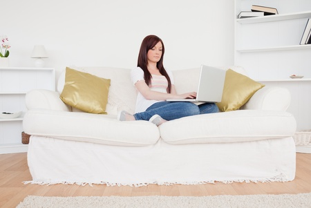 Good looking red-haired woman relaxing with her laptop while sitting on a sofa in the living room photo