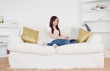 Pretty red-haired woman relaxing with her laptop while sitting on a sofa in the living room photo