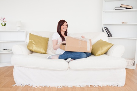 Attractive red-haired female opening a carboard box while sitting on a sofa in the living room photo