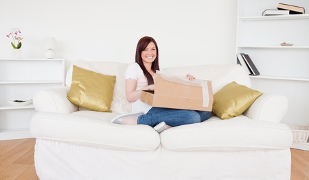 Beautiful red-haired female opening a carboard box while sitting on a sofa in the living room photo