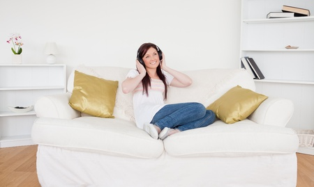 Beautiful red-haired female listening to music with headphones while sitting on a sofa in the living room photo