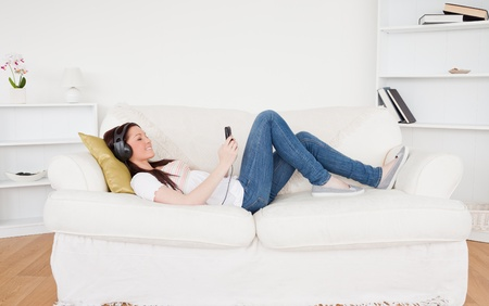 Attractive red-haired female listening to music with headphones while lying on a sofa in the living room Stock Photo - 10198106