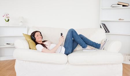 Beautiful red-haired female listening to music with headphones while lying on a sofa in the living room photo