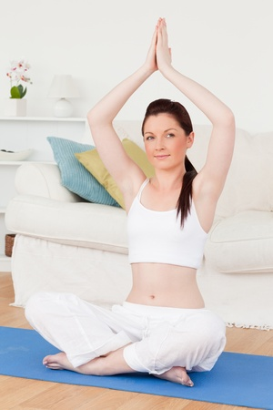 Smiling female doing yoga on a gym carpet in the living room Stock Photo - 10198668