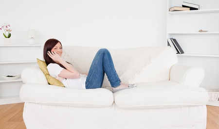 Beautiful red-haired woman having a conversation on the phone while lying on a sofa in the living room Stock Photo - 10197771
