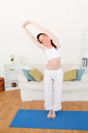 Charming red-haired woman stretching in the living room in her appartment Stock Photo - 10205900