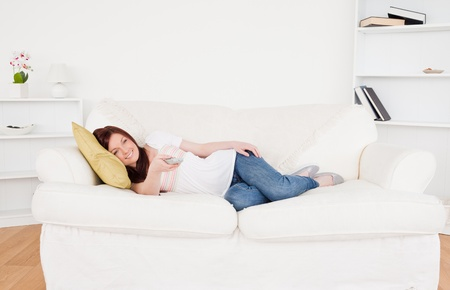 Attractive red-haired female watching tv while lying on a sofa in the living room photo