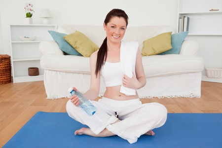 home gym: Beautiful female having a rest after stretching while sitting on a gym carpet in the living room Stock Photo