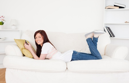 Good looking red-haired female writing a text on her phone while lying on a sofa in the living room Stock Photo - 10195746
