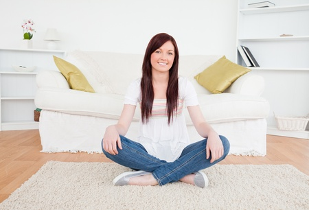 Beautiful red-haired female posing while sitting on a carpet in the living room photo