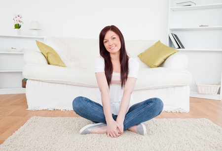 Good looking red-haired female posing while sitting on a carpet in the living room Stock Photo - 10206312