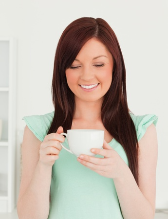 Attractive red-haired woman having her breakfast in the kitchen in her appartment photo