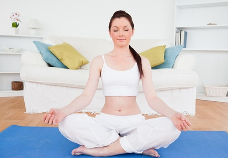 recreation room: Young female doing yoga on a gym carpet in the living room