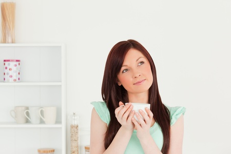 Pretty red-haired woman enjoying her breakfast in the kitchen in her appartment photo