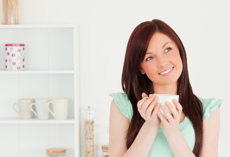 Attractive red-haired woman enjoying her breakfast in the kitchen in her appartment photo