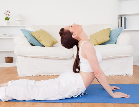 Charming red-haired female stretching in the living room in her appartment photo