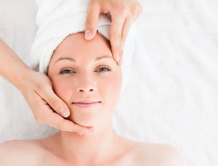 Closeup of a gorgeous red-haired woman receiving a massage in a spa centre photo