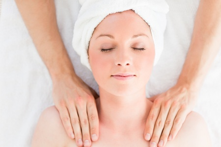 Closeup of a good looking red-haired woman receiving a massage in a spa centre photo