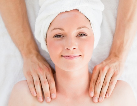 laying on back: Closeup of a cute red-haired woman receiving a massage in a spa centre Stock Photo