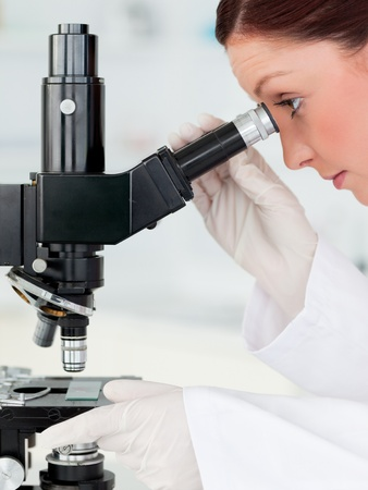 Good looking red-haired scientist looking through a microscope in a lab photo