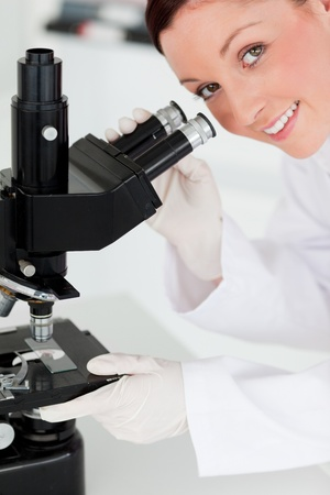 Charming red-haired scientist looking through a microscope in a lab photo