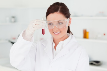 Cute red-haired scientist looking at a test tube in a lab photo
