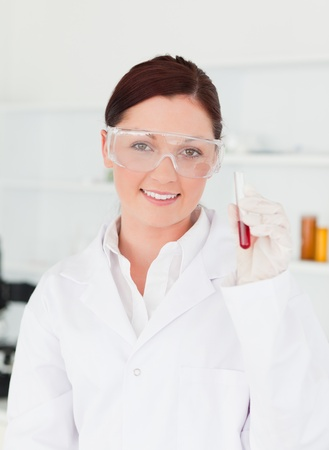 Smiling scientist looking at the camera while holding a  test tube in a lab Stock Photo - 10194858