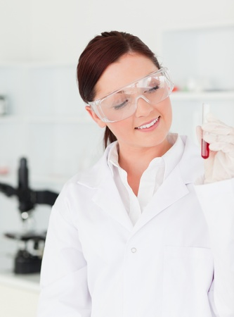 Pretty red-haired scientist looking at a test tube in a lab photo