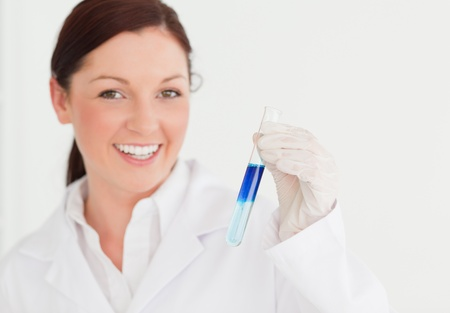 Smiling scientist looking at the camera while holding a  test tube in a lab photo