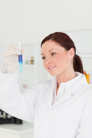 Attractive red-haired scientist looking at a test tube in a lab photo