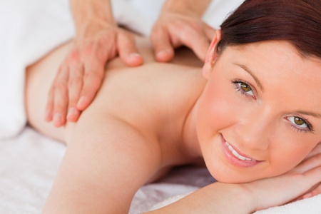 Closeup of a charming red-haired woman receiving a massage in a spa centre photo