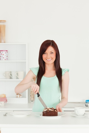 Beautiful red-haired woman cutting some cake in the kitchen in her appartment photo