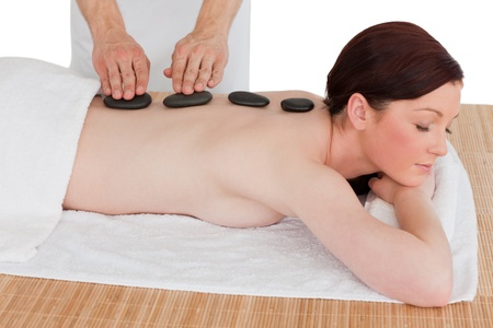 Portrait of a serene red-haired woman posing while receiving a massage in a spa centre photo