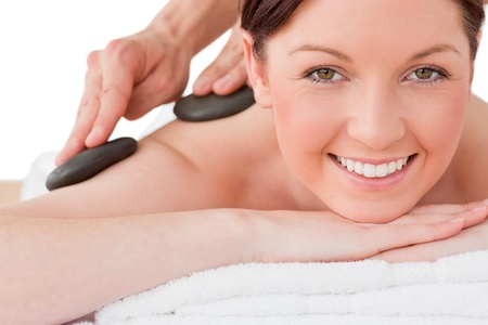 Portrait of a smiling red-haired female posing while receiving a massage in a spa centre photo