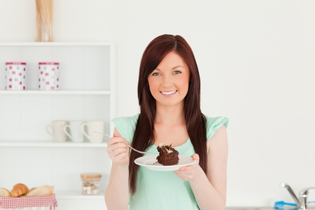 Good looking red-haired woman eating some cake in the kitchen in her appartment photo