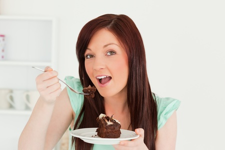 Charming red-haired woman eating some cake in the kitchen in her appartment photo