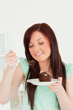 Joyful red-haired woman eating some cake in the kitchen in her appartment photo