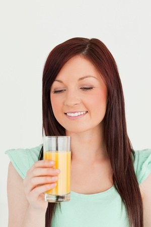 Gorgeous red-haired woman enjoying a glass of orange juice in the kitchen in her appartment photo